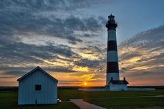 Lighthouse sunrise. Panoramic shot of the sunrise through early morning clouds at the Bodie Island Lighthouse in the Outer Banks of North Carolina Royalty Free Stock Images