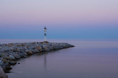 Lighthouse at Sunrise on the Rocky Coast. Dawning and Calm Sea in the Background Stock Image