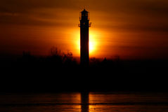 Lighthouse at the sunset. Lighthouse silhouette at the dark sunset in winter royalty free stock image
