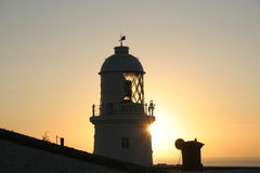 Lighthouse at Sunset. Lighthouse, Cornwall, England.  Silhouetted against setting sun Stock Images