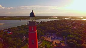 Lighthouse at sunset by Atlantic ocean stock video footage