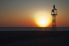 Lighthouse at sunset. Automatic lighthouse of the island on a beach at sunset Stock Image