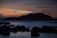Lighthouse at sunset with light beam Stock Image
