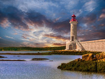 Lighthouse at sunset off a rocky coast. With calm ocean waters Royalty Free Stock Photos