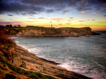 Lighthouse at sunset. Panoramic view of lighthouse and cliffs at sunset stock photo