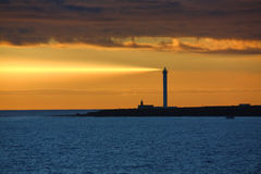 Lighthouse in Sunset with Ray of Light. Shining onto the Ocean - Metaphorical for Leading, Winning, Best Practice etc Royalty Free Stock Images