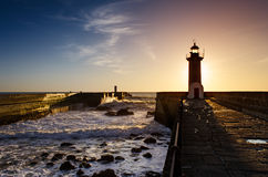 Lighthouse at sunset. Surrounded by the ocean Stock Images