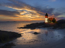 Lighthouse at sunset. With the tide coming in Stock Photography