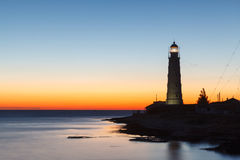 Lighthouse at sunset in the twilight in clear weather Stock Image