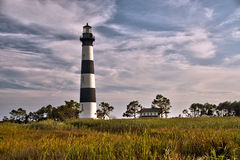 Lighthouse surrounded by clouds and marshland Royalty Free Stock Photo
