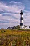 Lighthouse surrounded by clouds and marshland. Framed against a cloudy sky, marshland surrounds the Bodie Island Lighthouse in the Outer Banks of North Carolina Stock Images