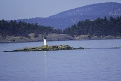 Light House In The Middle Of The Ocean. Lighthouse surrounded by water.  The mountains can also be seen in the distance, and closer to the light house evergreen royalty free stock photography