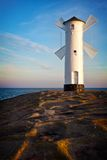 Lighthouse in Swinoujscie. White old lighthouse in Swinoujscie at sunrise, Poland Royalty Free Stock Images