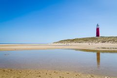 Lighthouse of Texel Netherlands. Lighthouse and beach of Texel with a clear blue sky. Texel is the largest wadden island in the Netherlands stock photo