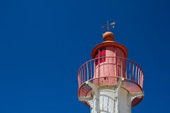 Lighthouse top. The upper part of a red lighthouse on a blue clear sky Royalty Free Stock Image
