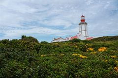 Lighthouse on top of cliff and surrounded by vegetation at Cape Espichel. Lighthouse on top of cliff and surrounded by vegetation under cloudy sky at Cape Stock Photos