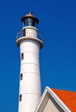 The lighthouse and top of the red roof with bright sky Royalty Free Stock Photography