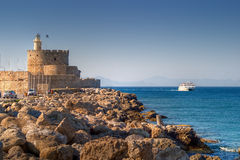 Lighthouse on a top of tower. Coast in Rhodes, Greece royalty free stock photography