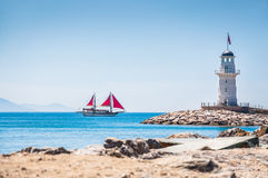 Lighthouse and tourist yacht by the sea Royalty Free Stock Images