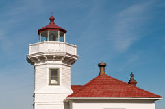 Lighthouse Tower and Roof Detail. Close-up of white tower housing lens and red roof of lighthouse in Mukilteo, Washington. Bright blue sky with wispy, white Stock Photo