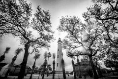 Lighthouse and Trees, black and white infrared. A lighthouse is framed by trees under a cloudy sky on a rainy day in this black and white infrared photo in Ponce Stock Photography