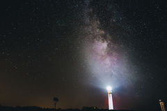 Lighthouse Turned on during Nighttime With Starry Skies Stock Images