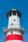 The lighthouse under clear blue sky in summer. The red and white lighthouse near the coast under clear blue sky in summer Royalty Free Stock Photo
