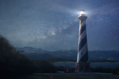 A lighthouse under night sky. A beautiful night sky behind a shining lighthouse Stock Photo