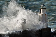 Lighthouse under the power of the waves Stock Photo