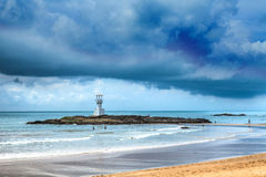 Lighthouse under Storm clouds over the sea Stock Photo