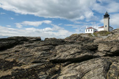Lighthouse on Unique Rock Formations. Beavertail Lighthouse guides mariners around dangerous rock formations in Rhode Island Royalty Free Stock Photos