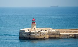 Lighthouse of Valletta port. Lighthouse in Valletta port of Malta on misty sea background with a ship Stock Photos