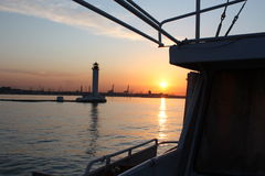 Lighthouse view from sea. Odessa port and lighthouse as seen from ship as the sun dips below the horizon Royalty Free Stock Image