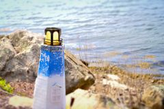 Lighthouse weathered miniature. A mini lighthouse mini against a lake or pond or garden backdrop background stock image