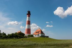 Nordfriesland. The lighthouse Westerheversand stands on a mound in front of the village Westerhever. The lighthouse is the landmark of the peninsula Eiderstedt stock photo