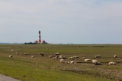Nordfriesland. The lighthouse Westerheversand stands on a mound in front of the village Westerhever. The lighthouse is the landmark of the peninsula Eiderstedt royalty free stock photo