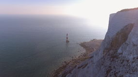 Lighthouse beside a white cliff. A unique lighthouse based on the south coast of England used to protect ships against the rocky coast stock video footage