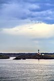 The lighthouse and white house, distant view Royalty Free Stock Image