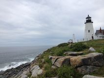 Lighthouse. White lighthouse on a rough cliff under blue sky Royalty Free Stock Photography