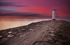 Lighthouse windmill with dramatic sunset sky Royalty Free Stock Photos