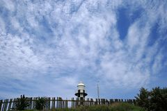 LIGHTHOUSE WITH WISPY CLOUDS Royalty Free Stock Photography