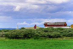Lighthouse, Wooden Barns and sailboat Royalty Free Stock Photo