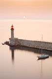Lighthouse and yacht in sunrise Stock Photography