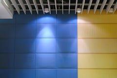 Lighting on backdrop. Shape of lighting on blue and yellow meeting room backdrop Stock Image
