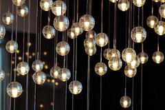 Lighting balls on the chandelier in the lamplight, light bulbs hanging from the ceiling, lamps on the dark background. Selective focus, horizontal Stock Photography
