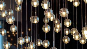 Lighting balls on the chandelier in the lamplight,  light bulbs hanging from the ceiling, lamps on the dark background, selective. Lighting balls on the Stock Image