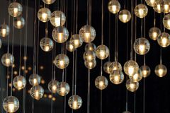 Lighting balls on the chandelier in the lamplight,  light bulbs hanging from the ceiling, lamps on the dark background, selective. Lighting balls on the Royalty Free Stock Image