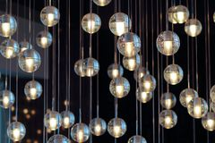 Lighting balls on the chandelier in the lamplight,  light bulbs hanging from the ceiling, lamps on the dark background, selective. Lighting balls on the Royalty Free Stock Photo