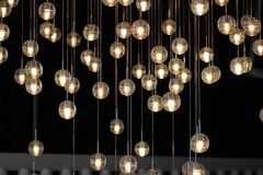 Lighting balls on the chandelier in the lamplight,  light bulbs hanging from the ceiling, lamps on the dark background, selective. Focus, horizontal Royalty Free Stock Photos