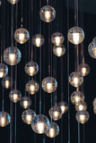Lighting balls on the chandelier in the lamplight. Light bulbs hanging from the ceiling, lamps on the dark background, selective focus, vertical Royalty Free Stock Photography